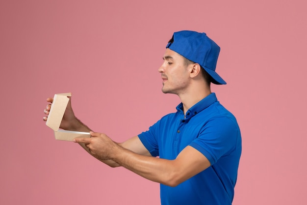 Vooraanzicht jonge mannelijke koerier in blauwe uniforme cape met een klein leeg pakket van het bezorgvoedsel op het roze bureau dat het bedrijf levert