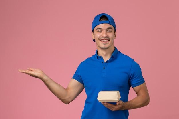 Vooraanzicht jonge mannelijke koerier in blauwe uniforme cape met levering voedselpakket lachend op roze muur