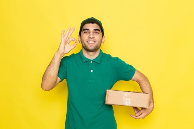 Vooraanzicht jonge mannelijke koerier in groen overhemd groen glb glimlachend en houdt leveringsdoos met goed teken op de gele achtergrond die dienstkleur levert