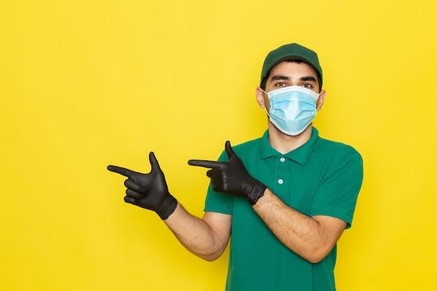 Vooraanzicht jonge mannelijke koerier in groen shirt groene pet zwarte handschoenen poseren op geel