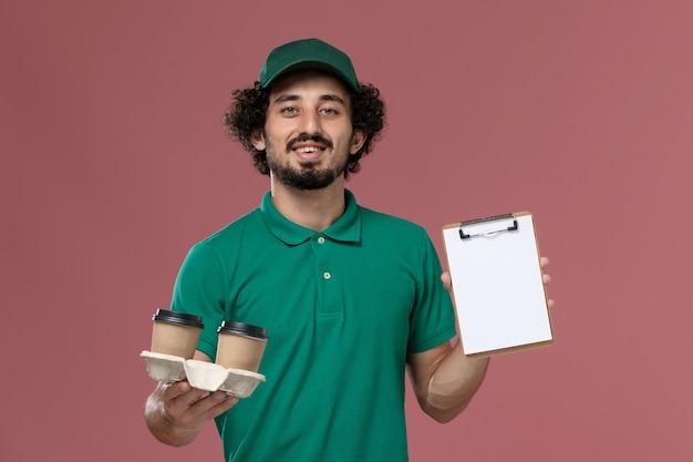 Vooraanzicht jonge mannelijke koerier in groen uniform en cape bedrijf levering koffiekopjes en blocnote op roze achtergrond mannelijke dienst baan uniforme levering