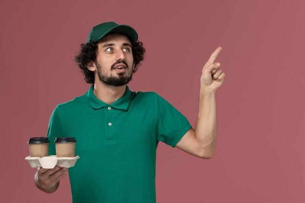 Vooraanzicht jonge mannelijke koerier in groen uniform en cape bedrijf levering koffiekopjes op de roze achtergrond dienst baan uniforme bezorger