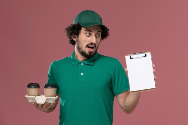 Vooraanzicht jonge mannelijke koerier in groen uniform en cape met levering koffiekopjes en blocnote op roze achtergrond mannelijke werknemer service uniforme levering