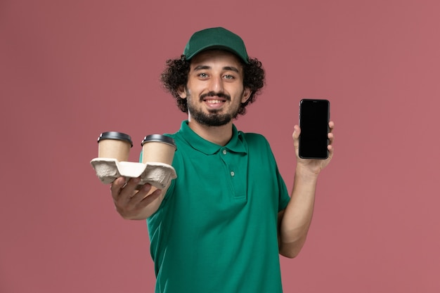 Vooraanzicht jonge mannelijke koerier in groen uniform en cape met telefoon en bezorgkoffiekopjes op de roze achtergronddienstbaan uniforme bezorger