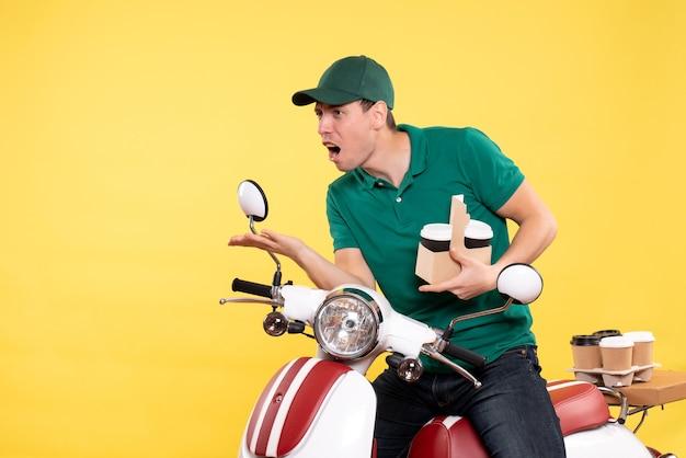 Vooraanzicht jonge mannelijke koerier in groen uniform met koffie op geel