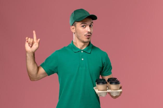 Vooraanzicht jonge mannelijke koerier in groene uniforme koffiekopjes houden die zijn vinger op roze achtergrond opheffen