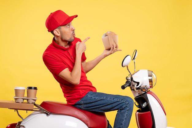 Vooraanzicht jonge mannelijke koerier in het rode uniforme voedsel van de holdingslevering op gele achtergrond