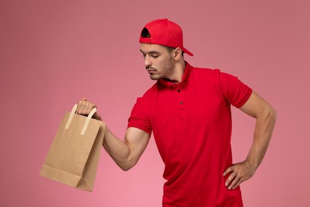 Vooraanzicht jonge mannelijke koerier in rode uniforme cape met papier voedselpakket op lichtroze achtergrond.