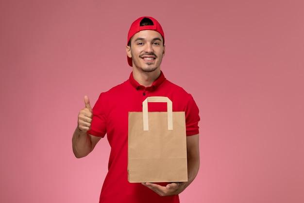 Vooraanzicht jonge mannelijke koerier in rode uniforme cape met papier voedselpakket op roze achtergrond.