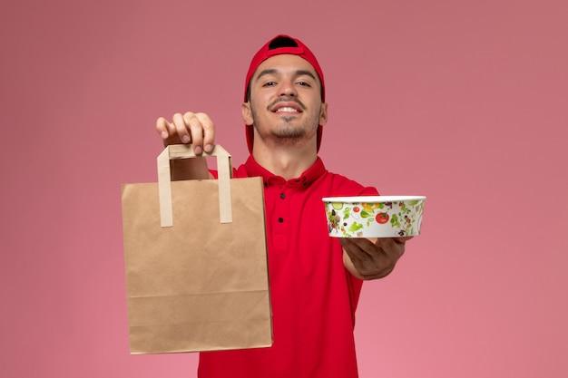 Vooraanzicht jonge mannelijke koerier in rode uniforme cape met voedselpakket en kom op de roze achtergrond.