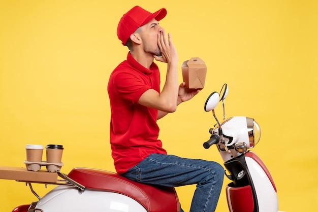Vooraanzicht jonge mannelijke koerier in rood uniform iemand luid bellen op gele achtergrond