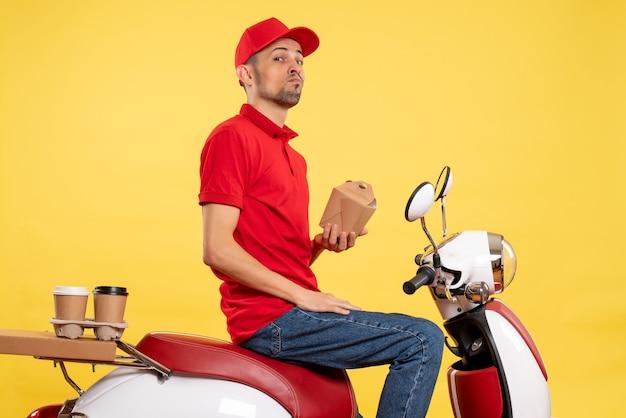 Vooraanzicht jonge mannelijke koerier in rood uniform op gele achtergrond Gratis Foto