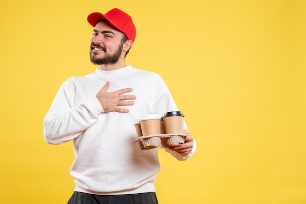 Vooraanzicht jonge mannelijke koerier met bezorgkoffie