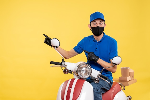 Vooraanzicht jonge mannelijke koerier op fiets in masker op gele achtergrond