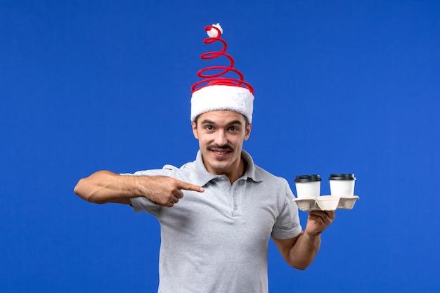 Vooraanzicht jonge mannelijke koffiekopjes houden op blauwe muur emoties mannelijk nieuwjaar