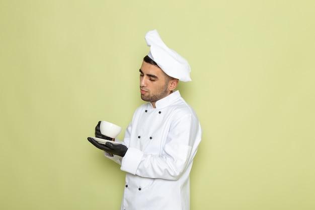 Vooraanzicht jonge mannelijke kok in de witte kop van de kokkostuum met koffie op groen