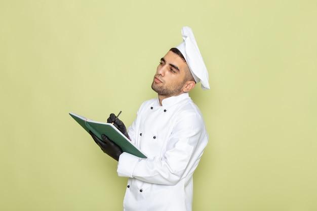 Vooraanzicht jonge mannelijke kok in wit kokkostuum die donkere handschoenen draagt en notities op groen opschrijft