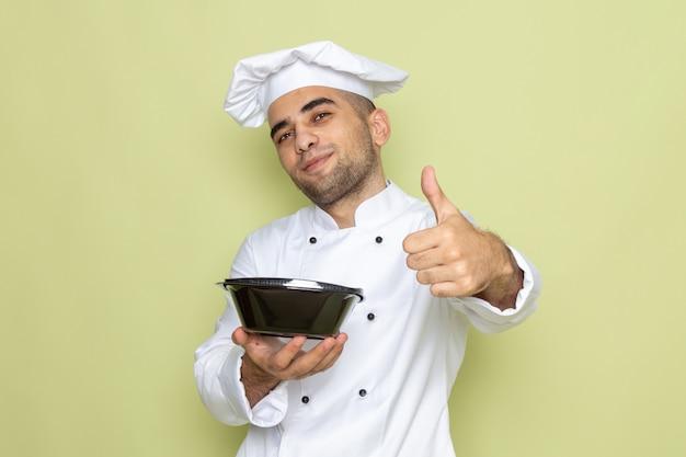 Vooraanzicht jonge mannelijke kok in wit kokkostuum die zwarte voedselkom houden en als teken op groen tonen