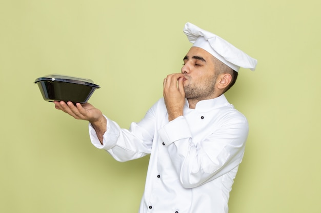 Vooraanzicht jonge mannelijke kok in wit kokkostuum die zwarte voedselkom op groen houden
