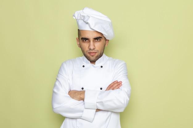 Vooraanzicht jonge mannelijke kok in wit kokkostuum stellen op een agressieve manier op groen