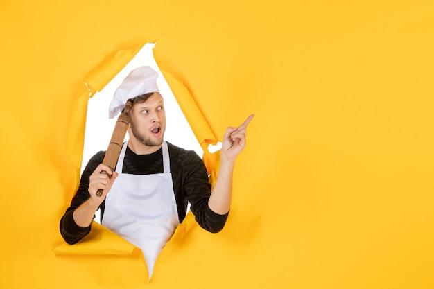 Vooraanzicht jonge mannelijke kok in witte cape met deegroller op gele achtergrond foto voedsel man keuken baan kleur wit