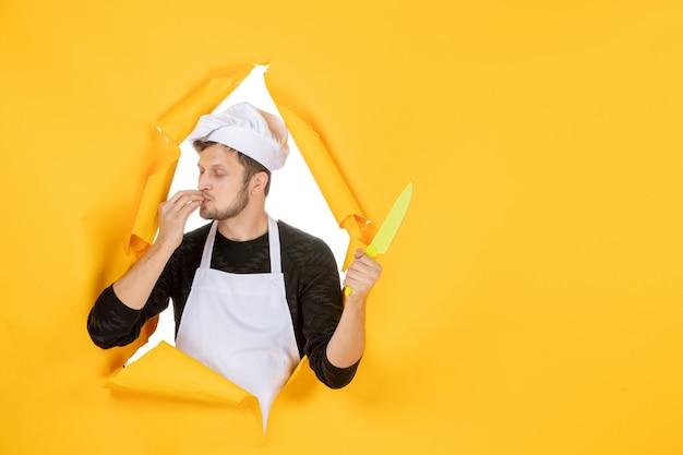 Vooraanzicht jonge mannelijke kok in witte cape op de gele achtergrond witte kleur keuken baan man voedsel foto keuken