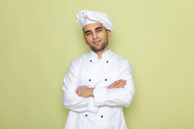Vooraanzicht jonge mannelijke kok in witte kok pak poseren met gekruiste armen op groen