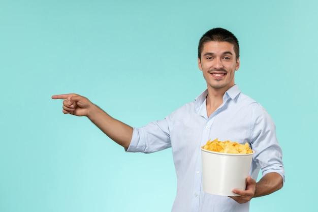 Vooraanzicht jonge mannelijke mand met chips en kijken naar film glimlachend op blauwe ondergrond