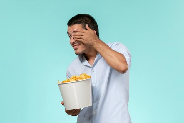 Vooraanzicht jonge mannelijke mand met chips en kijken naar film op blauwe ondergrond