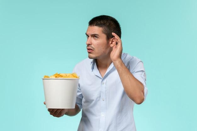 Vooraanzicht jonge mannelijke mand met chips en proberen te horen op een blauw oppervlak