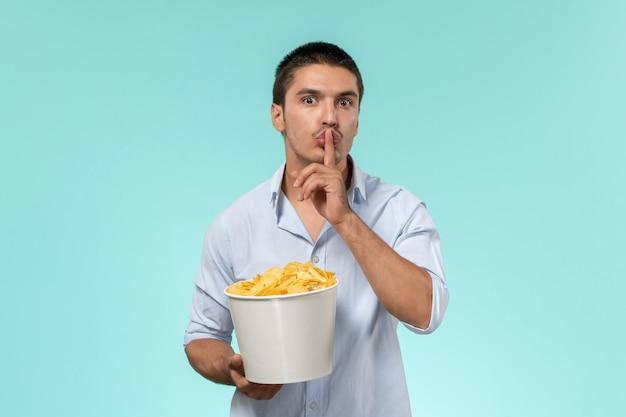 Vooraanzicht jonge mannelijke mand met chips en vragen om stil te zijn op een blauw oppervlak
