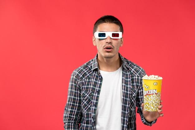 Vooraanzicht jonge mannelijke popcornpakket houden en kijken naar moive op lichtrode muur mannelijke bioscoop bioscoop film leuke tijden