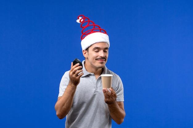 Vooraanzicht jonge mannelijke ruikende koffie op de blauwe emotie van de de mannelijke vakantie van het muur nieuwe jaar