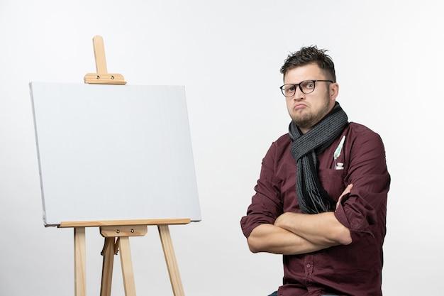 Vooraanzicht jonge mannelijke schilder samen met ezel op witte achtergrond