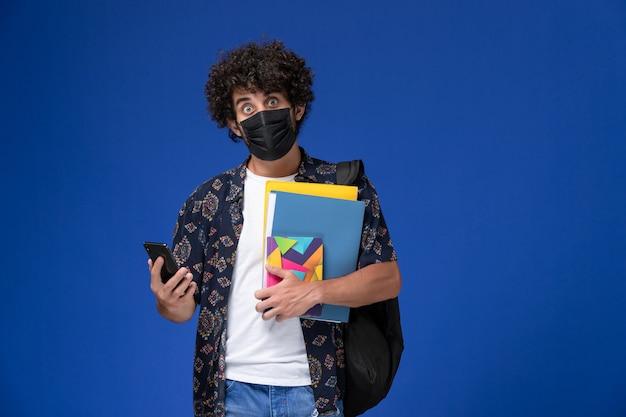 Vooraanzicht jonge mannelijke student die zwart masker met de dossiers van de rugzakholding en telefoon op de blauwe achtergrond draagt.
