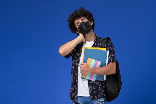 Vooraanzicht jonge mannelijke student die zwart masker met de dossiers van de rugzakholding en voorbeeldenboek draagt met nekpijn op blauw bureau.