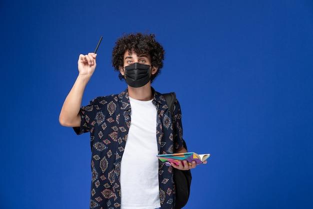 Vooraanzicht jonge mannelijke student die zwart masker met het voorbeeldenboek en de pen van de rugzakholding op blauw bureau draagt.