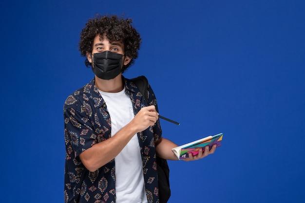 Vooraanzicht jonge mannelijke student die zwart masker met het voorbeeldenboek en de pen van de rugzakholding op de blauwe achtergrond draagt.