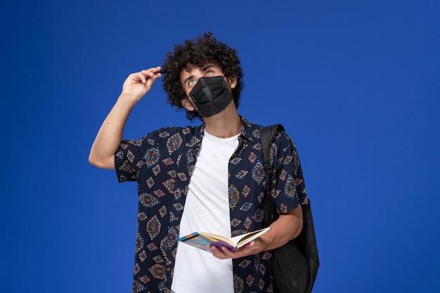 Vooraanzicht jonge mannelijke student die zwart masker met het voorbeeldenboek van de rugzakholding draagt die op het blauwe bureau denken.