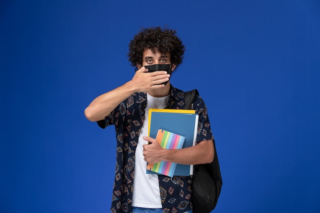 Vooraanzicht jonge mannelijke student die zwart masker met het voorbeeldenboek van de rugzakholding en dossiers op het blauwe bureau draagt.