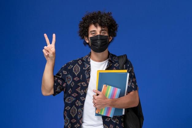 Vooraanzicht jonge mannelijke student die zwart masker met rugzak draagt die voorbeeldenboek en dossiers op de lichtblauwe achtergrond houdt.
