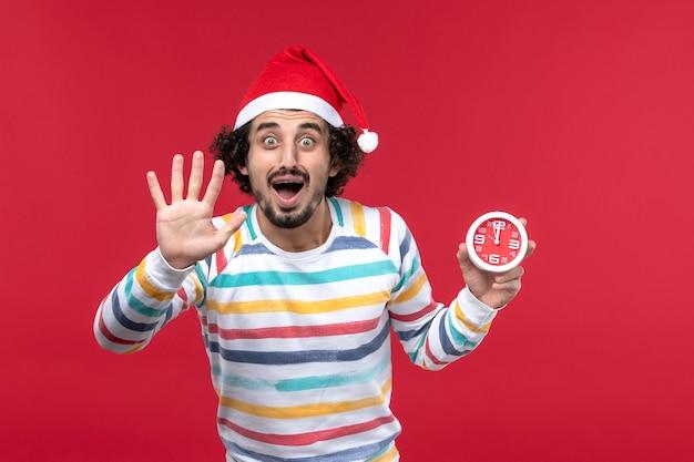 Vooraanzicht jonge mannelijke tellen nummer op rode muur rode tijd nieuwjaar vakantie