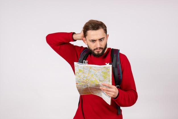 Vooraanzicht jonge mannelijke toerist die met rugzak kaart op wit van de de stadsvakantie van het muurvliegtuig onderzoekt de emotie menselijk kleurentoerisme