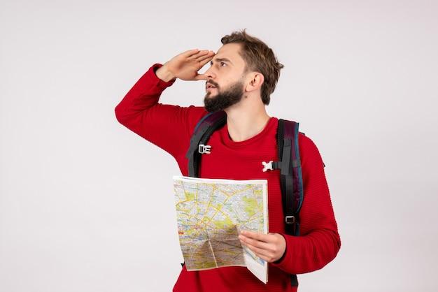 Vooraanzicht jonge mannelijke toerist die met rugzak kaart op witte van de de stadsvakantie emotie menselijke toerismeroute van het muurvliegtuig onderzoekt