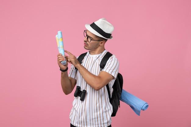 Vooraanzicht jonge mannelijke toerist met kaarten op de roze achtergrond