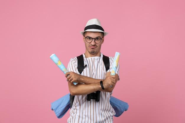 Vooraanzicht jonge mannelijke toerist met kaarten op roze bureau