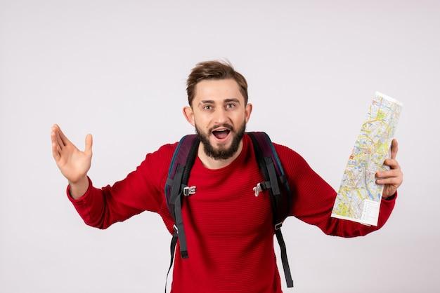 Vooraanzicht jonge mannelijke toerist met rugzak verkennen kaart op witte muur covid vliegtuig vakantie emotie virus vlucht kleuren