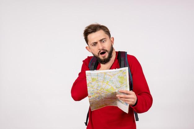 Vooraanzicht jonge mannelijke toerist met rugzak verkennen kaart op witte muur vliegtuig stad vakantie emotie menselijke kleur toerisme route