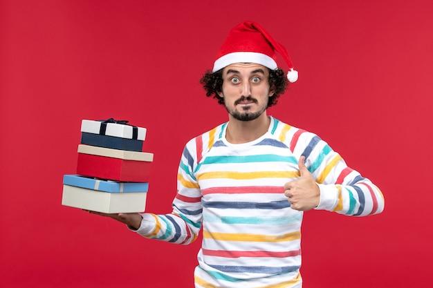 Vooraanzicht jonge mannelijke vakantie presenteert op rode muur vakantie nieuwjaar emoties