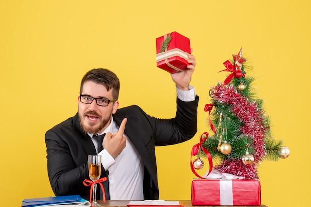 Vooraanzicht jonge mannelijke werknemer achter zijn tafel met cadeautjes en kerstboom op geel